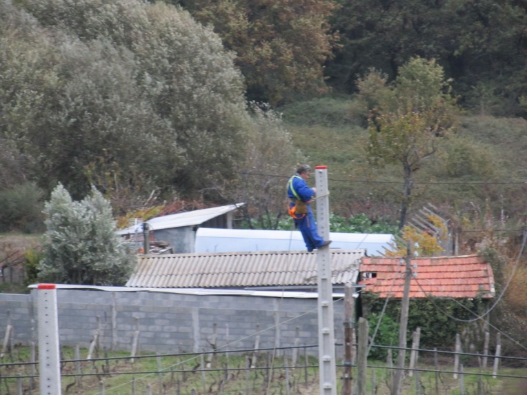 Trabajador desempeñando sus labores al tope de un poste de hormigón