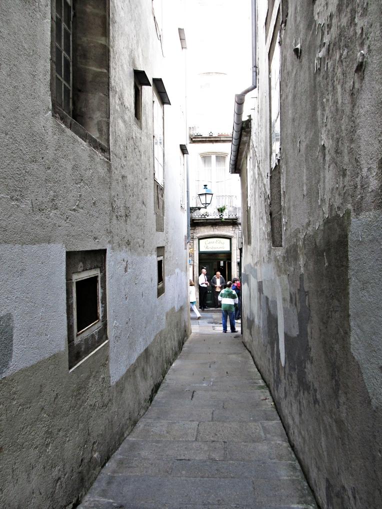 Estrecha callejuela medieval en Santiago de Compostela; al fondo, restaurante. Mediodía - tarde del 12 de octubre, 2012